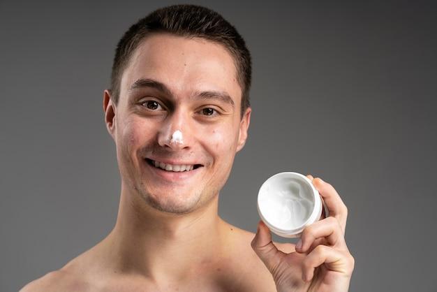 にきびのためのクリームを使用して若いハンサムな男