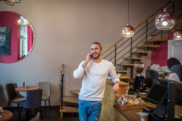 Молодой красавец с помощью телефона в кафе