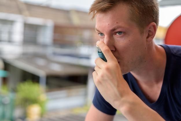 自宅で喘息の吸入器を使用して若いハンサムな男