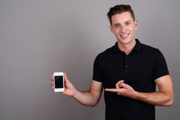 Young handsome man using mobile phone on gray