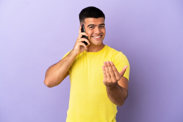 Young handsome man using mobile phone over isolated purple background inviting to come with hand. happy that you came