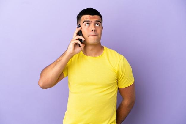 孤立した紫色の背景の上に携帯電話を使用して見上げる若いハンサムな男