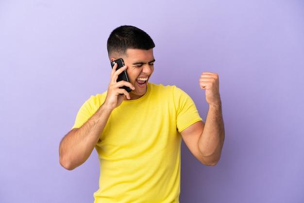 Молодой красавец с помощью мобильного телефона на изолированном фиолетовом фоне празднует победу