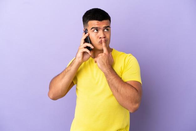 Молодой красавец, использующий мобильный телефон на изолированном фиолетовом фоне, сомневается, глядя вверх