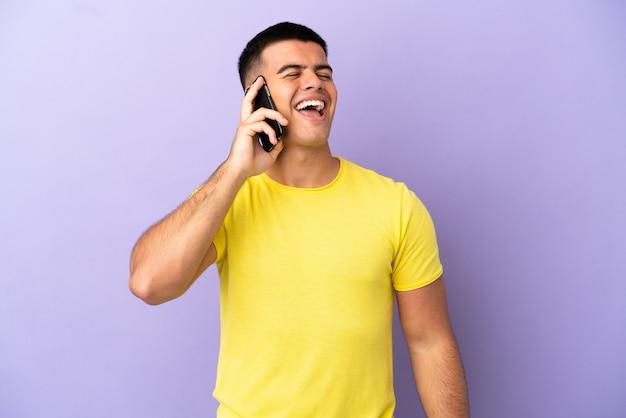 Молодой красивый мужчина с помощью мобильного телефона на изолированном фиолетовом фоне смеется