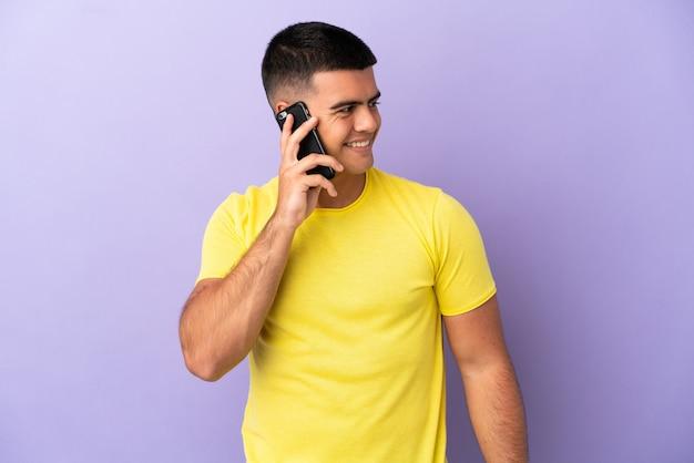Молодой красивый мужчина с помощью мобильного телефона на изолированном фиолетовом фоне, глядя в сторону