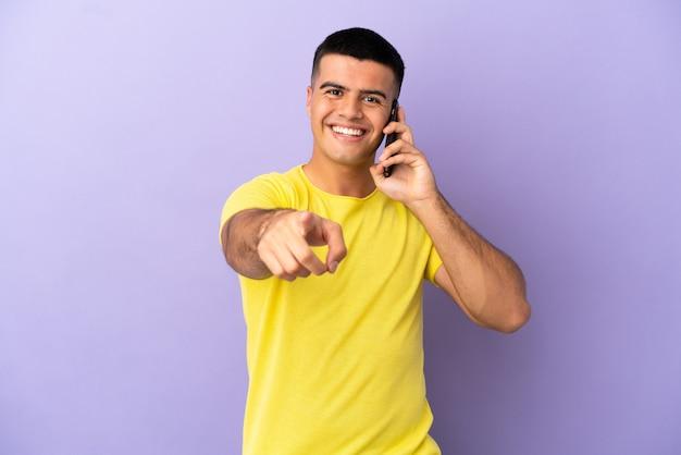 행복 한 표정으로 앞을 가리키는 고립 된 보라색 배경 위에 휴대 전화를 사용 하는 젊은 잘생긴 남자