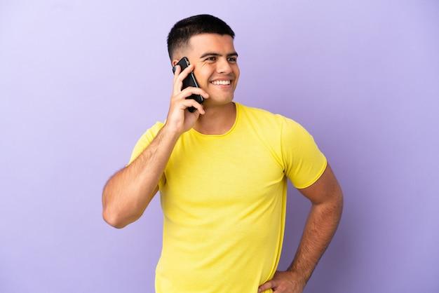 Молодой красивый мужчина с помощью мобильного телефона на изолированном фиолетовом фоне позирует с руками на бедрах и улыбается