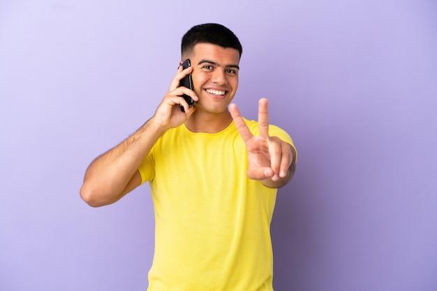 Молодой красавец с помощью мобильного телефона на изолированном фиолетовом фоне улыбается и показывает знак победы