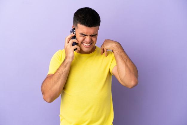 Молодой красавец, использующий мобильный телефон на изолированном фиолетовом фоне, страдает от боли в плече за то, что приложил усилия