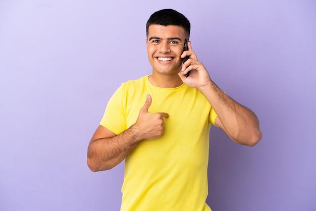 Молодой красавец, использующий мобильный телефон на изолированном фиолетовом фоне с удивленным выражением лица
