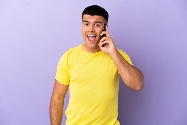 놀란 표정으로 고립된 보라색 배경 위에 휴대전화를 사용하는 젊고 잘생긴 남자