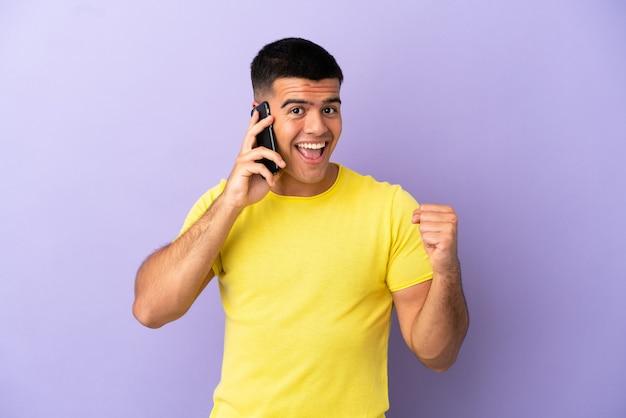 Молодой красавец, использующий мобильный телефон над изолированной фиолетовой стеной, празднует победу в позиции победителя