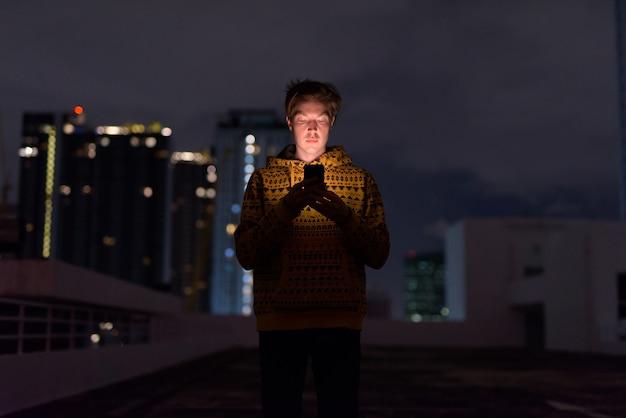 夜の荒天時に街の景色に対して電話を使用して若いハンサムな男
