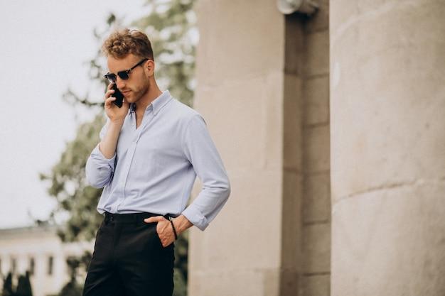 通りで電話を使用して若いハンサムな男 無料写真