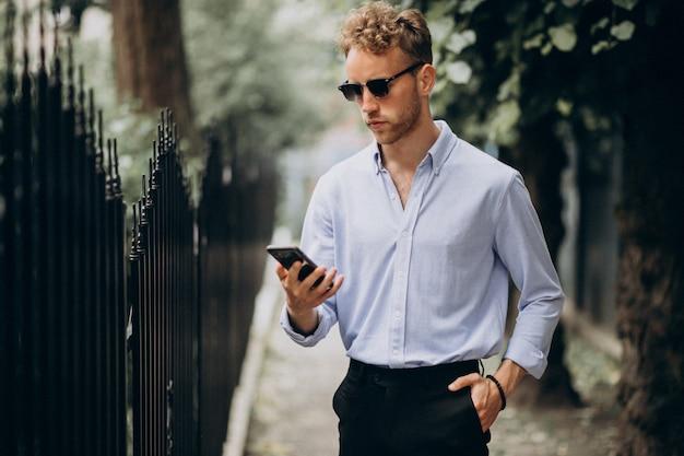 Giovane uomo bello che utilizza telefono fuori nella via