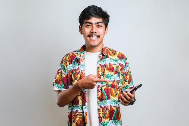 カジュアルなシャツを着てスマートフォンを使用して若いハンサムな男は、手と指で非常に幸せなポインティング電話白い背景を分離しました