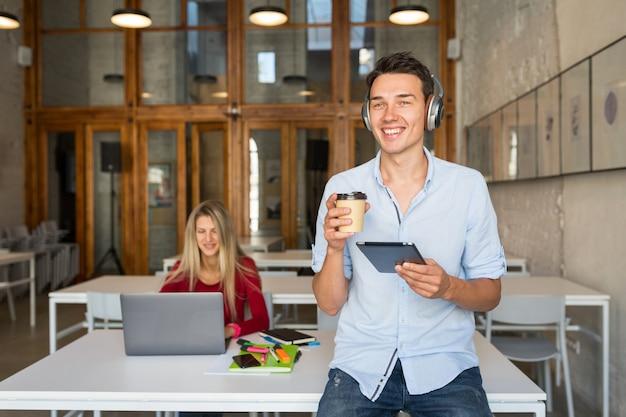 Giovane uomo bello utilizzando tablet ascoltando musica su cuffie wireless,