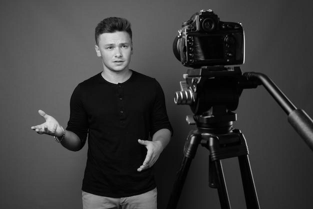 灰色の壁に向かってビデオブログをしている若いハンサムな男。黒と白