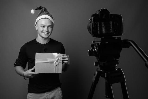 若いハンサムな男は、灰色の壁に対してクリスマスの準備ができています。黒と白