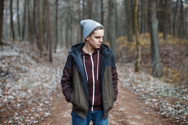 Young handsome man walking in the autumn forest