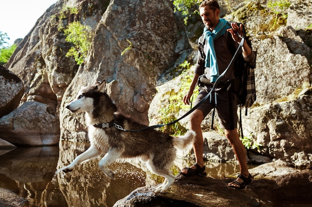 Young handsome man walking with huskies dog in canyon near water