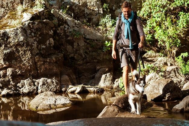 Молодой красивый человек гуляя с собакой хаски в каньоне около воды