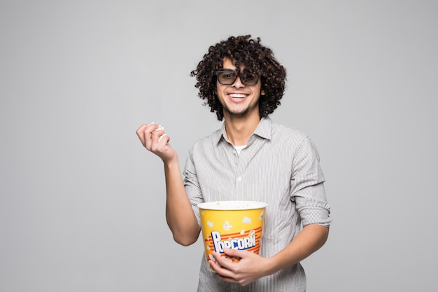Young handsome man wear 3d glasses with curly hair holding a bowl of popcorns over isolated white wall