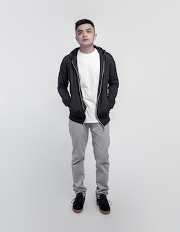スペースに分離された黒のパーカーと白いtシャツを着ている若いハンサムな男