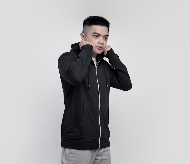 Young handsome man wearing black hoodie zipper isolated on wall