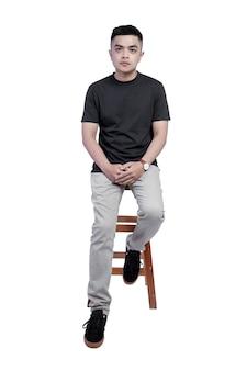 黒のtシャツの半袖を着ている若いハンサムな男が椅子に座っていた