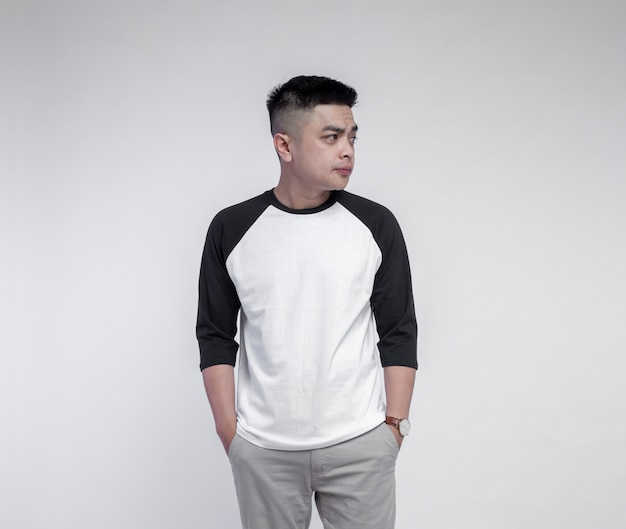 Young handsome man wearing black white raglan t-shirt isolated on background