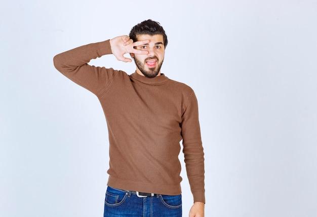 Молодой красавец в коричневом свитере на белой стене, делая v-знак возле глаз. фото высокого качества