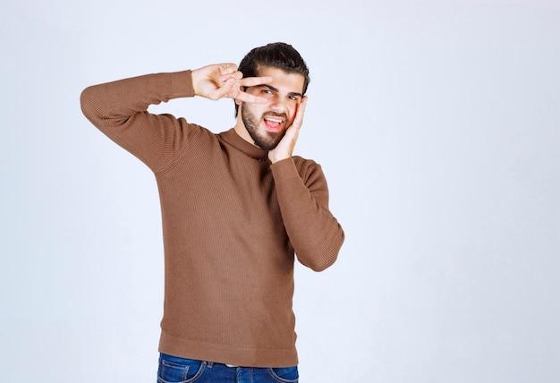 目の近くにvサインを作る白い壁に茶色のセーターを着ている若いハンサムな男。