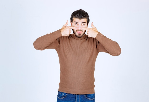 Молодой красавец в повседневной одежде, указывая пальцем на лицо и нос.