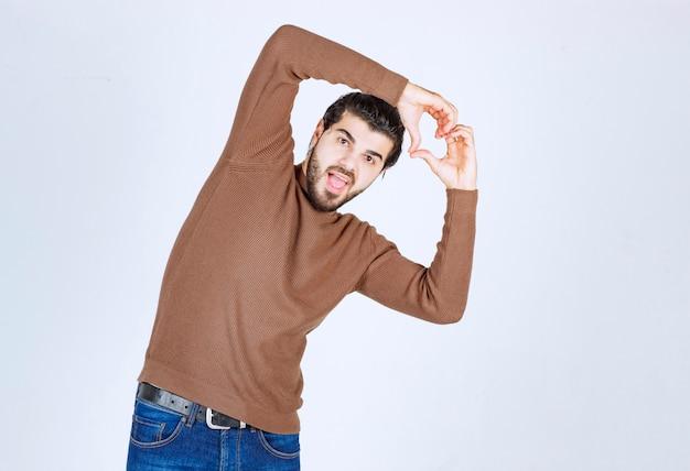 웃 고 손으로 심장 기호 모양을 하 고 캐주얼 옷을 입고 젊은 잘 생긴 남자. 고품질 사진