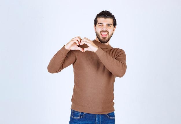 笑顔でカジュアルな服を着て、手でハートのシンボルの形をしている若いハンサムな男。高品質の写真