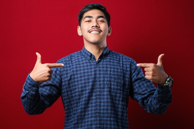 Young handsome man wearing casual shirt looking confident with smile on face, pointing oneself with fingers proud and happy over red background