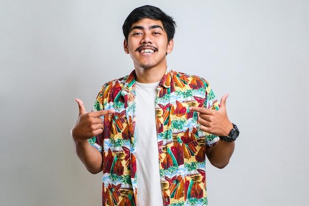 カジュアルなシャツを着て、笑顔で自信を持って見える若いハンサムな男は、白い背景の上に誇らしげに幸せな指で自分を指しています