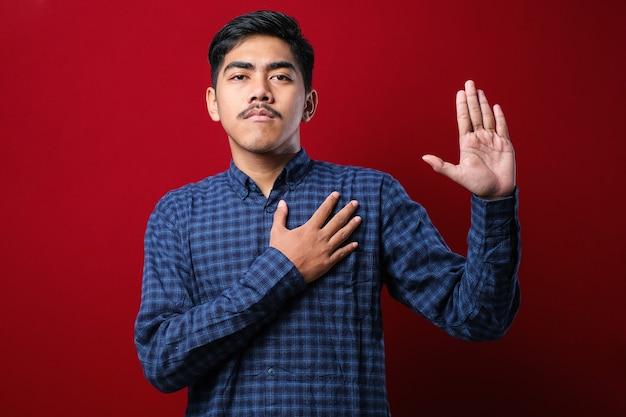 외진 붉은 배경 위에 캐주얼 셔츠를 입은 젊고 잘생긴 남자는 가슴에 손을 대고 손바닥으로 맹세하며 충성을 맹세합니다.