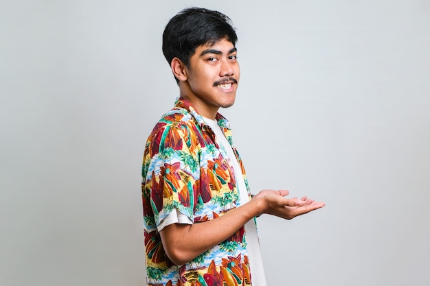 孤立した白い背景の上にカジュアルなシャツを着て、コピースペースを示す手のひらを開いて脇を指して、幸せに興奮して笑顔の広告を提示する若いハンサムな男