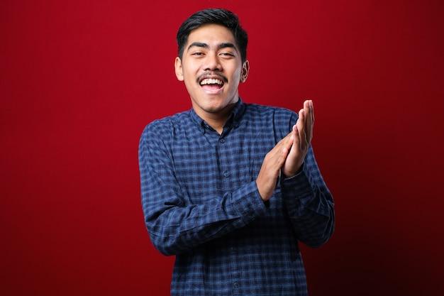 빨간 배경 위에 캐주얼 셔츠를 입은 젊고 잘생긴 남자는 박수를 치고 행복하고 즐거운 박수를 보내며 자랑스러운 손을 함께 웃고 있다