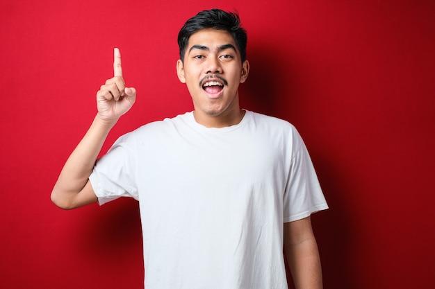 赤い背景の上にカジュアルなシャツを着ている若いハンサムな男1本の指で頭を指して笑顔、素晴らしいアイデアや考え、良い思い出
