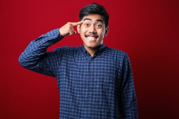빨간 배경 위에 캐주얼 셔츠를 입은 젊고 잘생긴 남자 한 손가락으로 머리를 가리키며 웃고, 좋은 아이디어나 생각, 좋은 기억