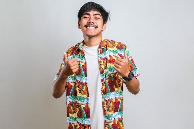 白い背景の上にカジュアルなシャツを着ている若いハンサムな男は、手で前向きなジェスチャーをすることを承認し、笑顔で成功を喜んで親指を立てます。勝者のジェスチャー。