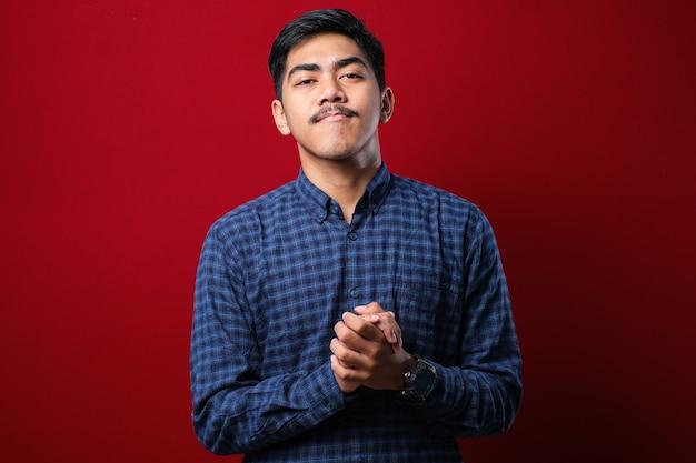 カジュアルなシャツを着て、孤立した赤い背景の上に手を一緒に立って、リラックスして陽気な笑顔で指を交差させた若いハンサムな男。成功と楽観的