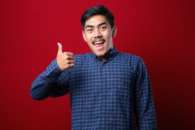 캐주얼 셔츠를 입은 젊고 잘생긴 남자는 손으로 행복한 엄지손가락을 치켜드는 고립된 redbackground 위에 서 있습니다. 성공을 보여주는 카메라를 보고 있는 식을 승인합니다.