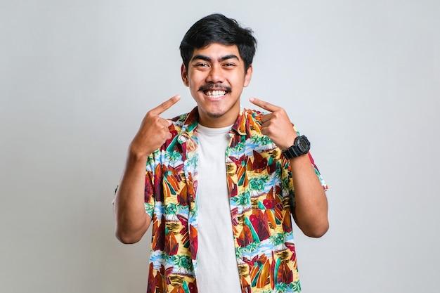 Молодой красивый мужчина в повседневной рубашке, стоящий на изолированном белом фоне, улыбается веселый показ и указывая пальцами, зубами и ртом. концепция стоматологического здоровья.