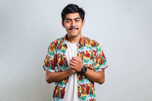 一緒に手と交差した指でリラックスして陽気な笑顔で孤立した白い背景の上に立っているカジュアルなシャツを着ている若いハンサムな男。成功と楽観的