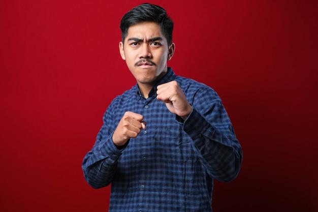 붉은 배경 위에 서 있는 캐주얼 셔츠를 입은 젊고 잘생긴 남자가 주먹을 휘두르며 싸우고, 공격적이고 화난 공격, 위협, 폭력
